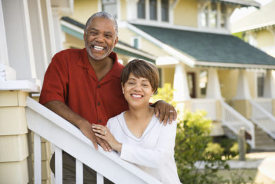 African American middle aged couple standing together on stairs outside home.